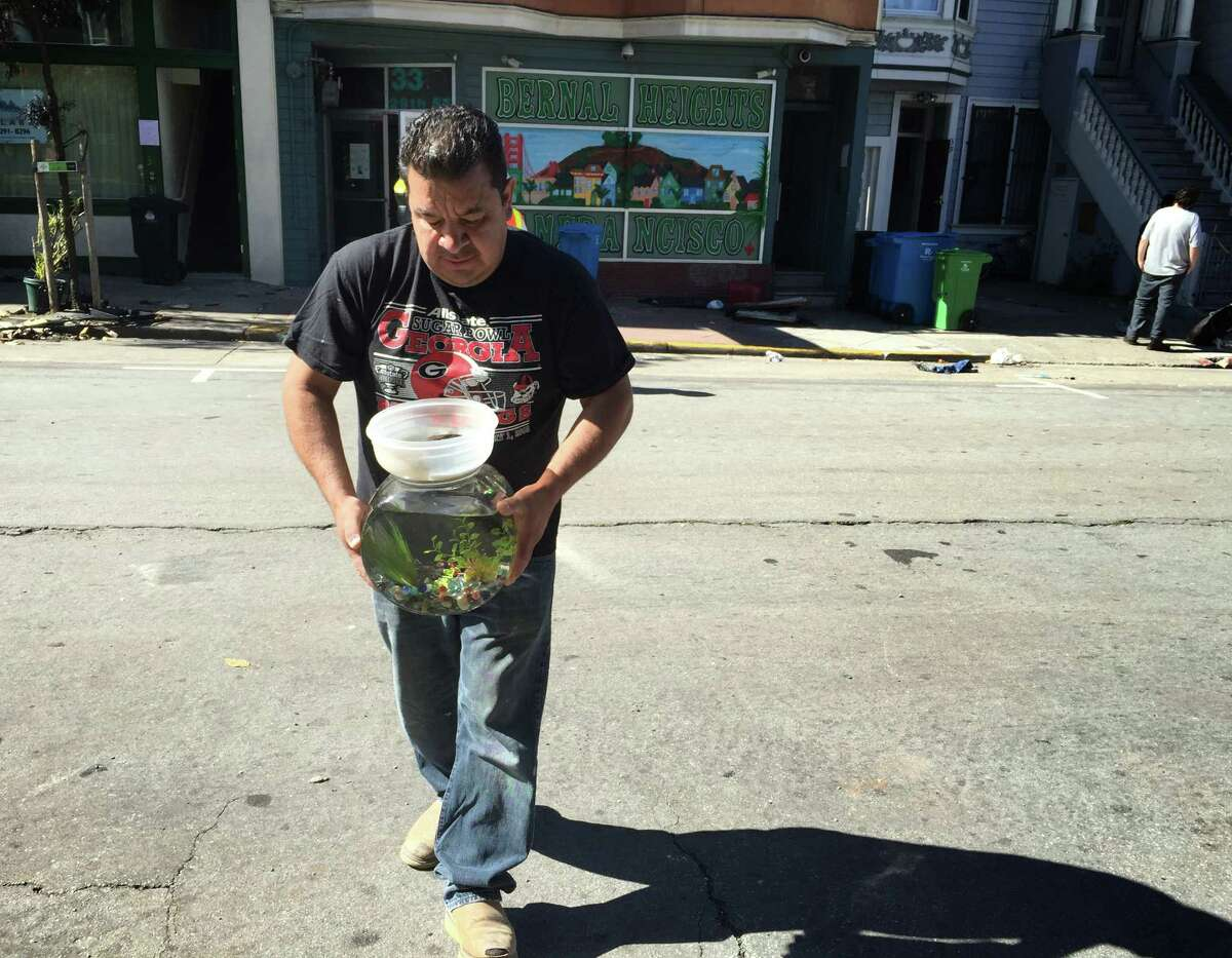 A resident at 37 29th St. in San Francisco pulls a turtle and fishbowl from his home on Monday. The building suffered water damage from Saturday's five-alarm fire in the Outer Mission District.