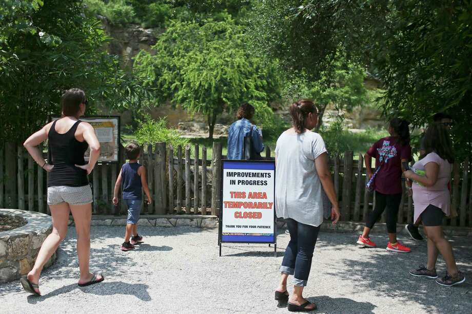 Zoo visitors walk by the exhibit for the lions, which have been moved in with the tigers as the lions exhibit gets a spruced-up living space. Photo: Jerry Lara /San Antonio Express-News / © 2016 San Antonio Express-News