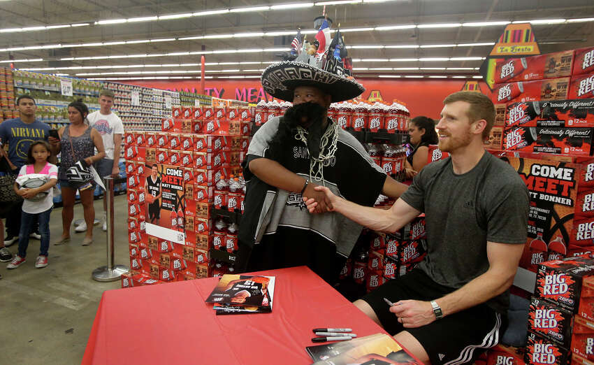 San Antonio Spurs forward Matt Bonner (right) poses for a picture after signing an autograph Monday June 20, 2016 for a fan who identified himself as Spurachi Carrasco (center, wearing hat) at the La Fiesta Supermarket on Ingram Road. Bonner was there to mingle with fans, sign autographs and promote Big Red soda.