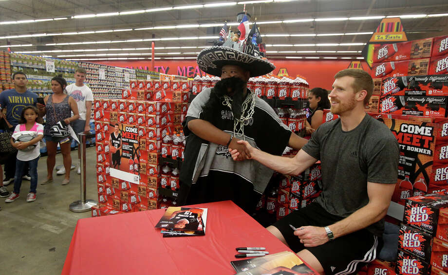 San Antonio Spurs forward Matt Bonner (right) poses for a picture after signing an autograph Monday June 20, 2016 for a fan who identified himself as Spurachi Carrasco (center, wearing hat) at the La Fiesta Supermarket on Ingram Road. Bonner was there to mingle with fans, sign autographs and promote Big Red soda. Photo: John Davenport, San Antonio Express-News / ©San Antonio Express-News/John Davenport