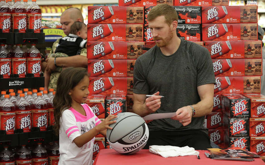 San Antonio Spurs forward Matt Bonner (right) signs an autograph Monday June 20, 2016 for Delilah Benn,8, (left) at the La Fiesta Supermarket on Ingram Road. Bonner was there to mingle with fans, sign autographs and promote Big Red soda.
