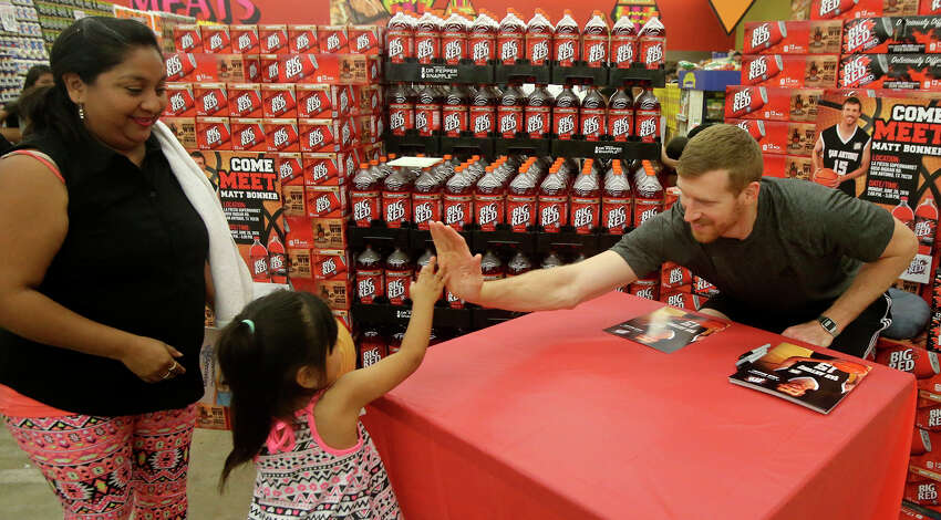 San Antonio Spurs forward Matt Bonner (right) exchanges high fives with Espernaza Hernandez,4, before signing an autograph Monday June 20, 2016 at the La Fiesta Supermarket on Ingram Road. Bonner was there to mingle with fans, sign autographs and promote Big Red soda. On the far left is Esperanza's mom Maria.