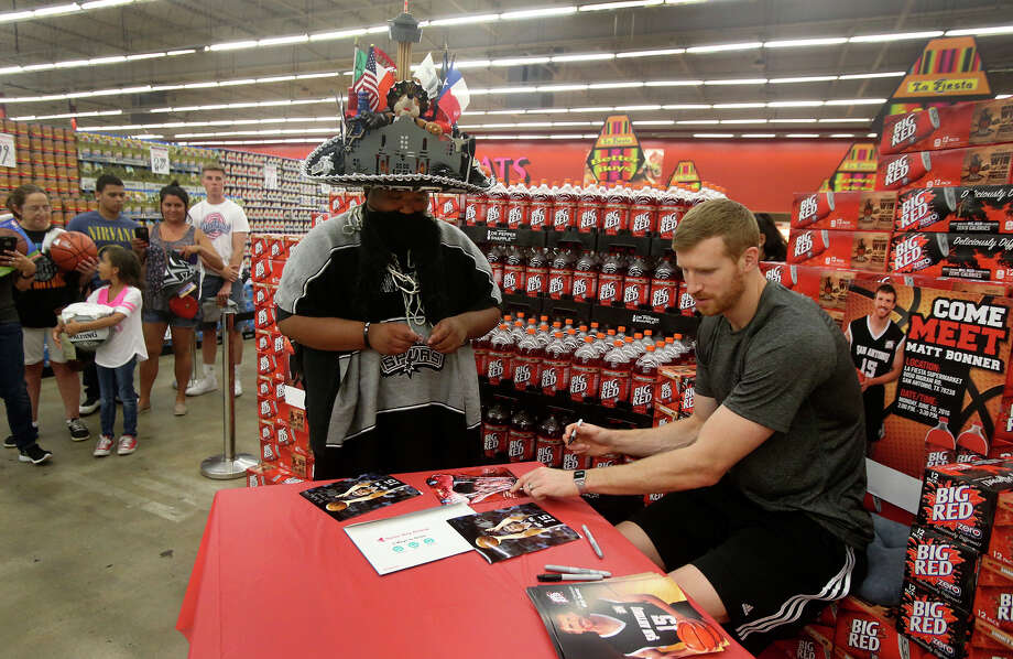 """San Antonio Spurs forward Matt Bonner (right) signs an autograph on June 20, 2016 for a fan who identified himself as """"Spurachi Carrasco"""" (center, wearing hat) at the La Fiesta Supermarket on Ingram Road. Bonner was there to mingle with fans, sign autographs and promote Big Red soda. Photo: John Davenport /San Antonio Express-News / ©San Antonio Express-News/John Davenport"""