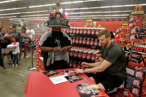 "San Antonio Spurs forward Matt Bonner (right) signs an autograph on June 20, 2016 for a fan who identified himself as ""Spurachi Carrasco"" (center, wearing hat) at the La Fiesta Supermarket on Ingram Road. Bonner was there to mingle with fans, sign autographs and promote Big Red soda."