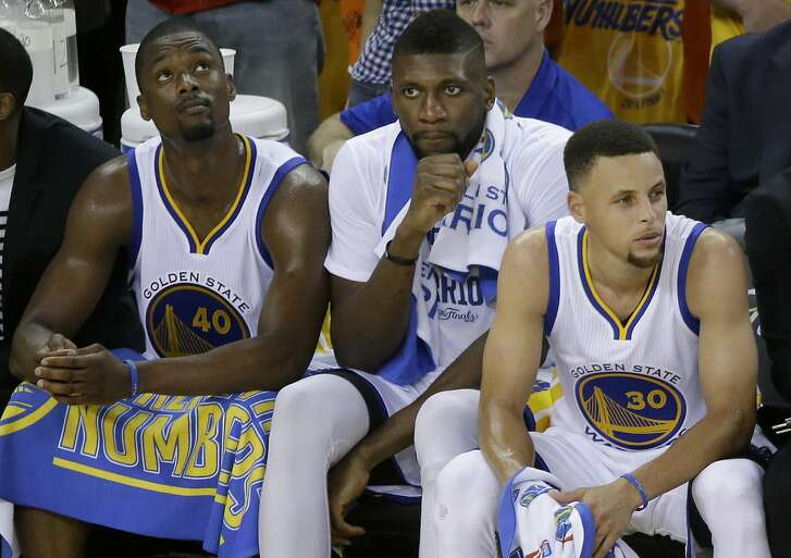 Golden State Warriors forward Harrison Barnes, from left, center Festus Ezeli and guard Stephen Curry sit on the bench during the second half of Game 5 of basketball's NBA Finals against the Cleveland Cavaliers in Oakland, Calif., Monday, June 13, 2016. The Cavaliers won 112-97. (AP Photo/Eric Risberg)