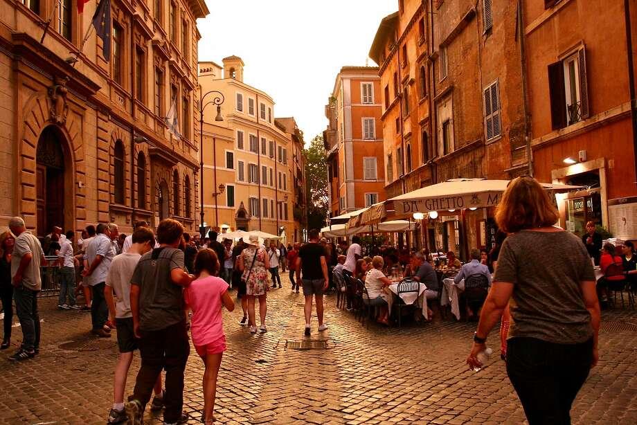 Pedestrians on the Via del Portico d'Ottavia, in Rome's Jewish Ghetto.