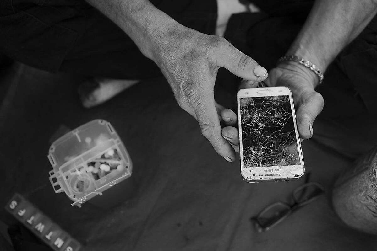"""Tony Cook, who has lived on the streets of San Francisco for almost 39 years, tries to use his broken cell phone on Wednesday, June 9, 2016 in San Francisco, Calif. Sitting next to him is a box of used needles. He said he uses methamphetamine once a day, usually in the morning, like a cup of coffee. """"I drink coffee too,"""" he said. While many discard needles on the streets, Cook said he likes to keep it clean and disposes of them properly. """"Sometimes I even pick up other people's needles."""""""