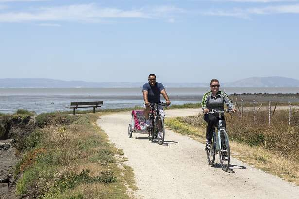 Bicyclists use a trail at the Hayward Regional Shoreline in Hayward, Calif., on Saturday, June 11, 2016. The park is located on a former commercial salt flat and is now a reclaimed wetland area.