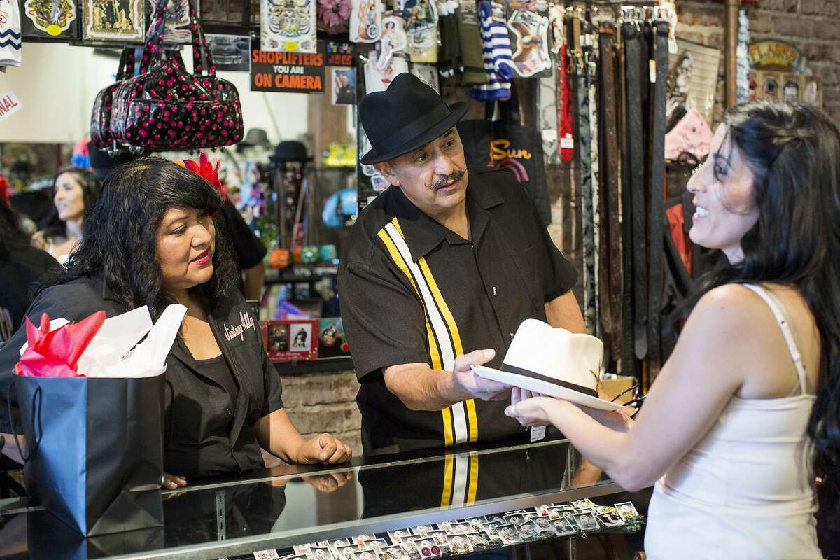 Rosanna Honahnie (left) and Alfredo Rodriguez, the owner of Vintage Alley, help Tanya Gutierrez pick out a hat to buy her dad for Father's Day at the store in downtown Hayward, Calif., on Saturday, June 11, 2016. The shop is a combination of a retail store for vintage inspired clothing and a beauty salon.