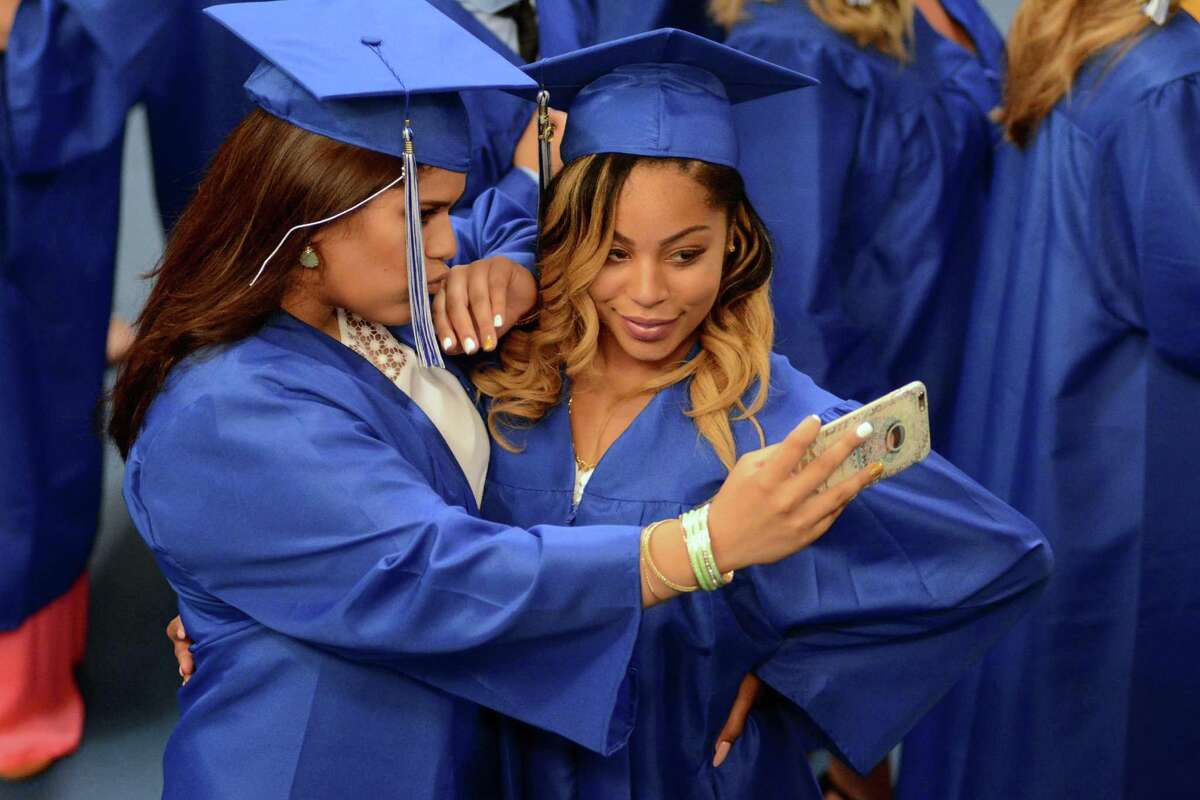 Raquel Diaz, left, and Celine Spinks pose for a selfie before Henry Abbott Technical High School Commencement ceremony at the O'Neill Center at WCSU on Monday, June, 20, 2016.