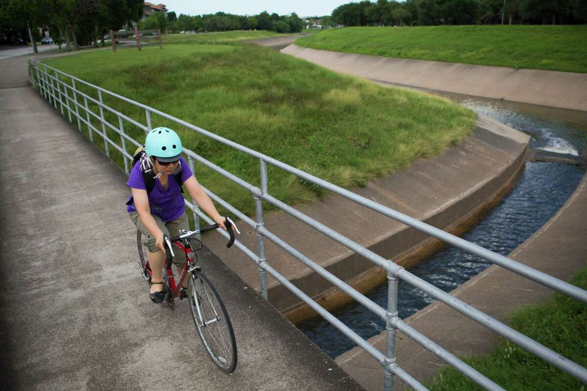 A bicycle rider travels along Brays Bayou on June 20, 2016.