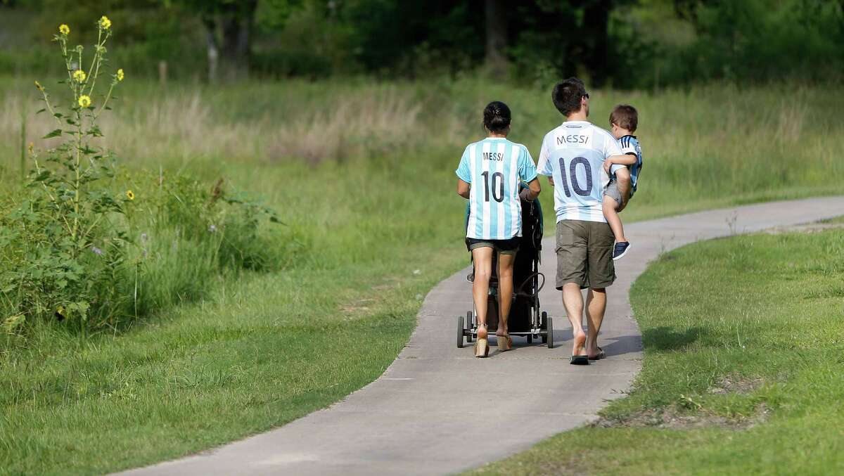 Fans of Lionel Messi wear his jersey as they walk around the closed off Argentina men's soccer practice at Rice University, Monday, June 20, 2016, in Houston, as they prepare to face the US, Tuesday night.