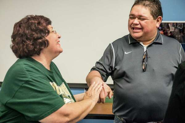 Josie Scales, a member of the Harlandale PTA Council, left, shakes the hand of Raul Navaira, brother of the late Tejano star Emilio Navaira, on June 1, when the Harlandale ISD board of trustees meeting took no action on a proposal to rename Vestal Elementary after the bandleader. The board again postponed a decision Monday evening.