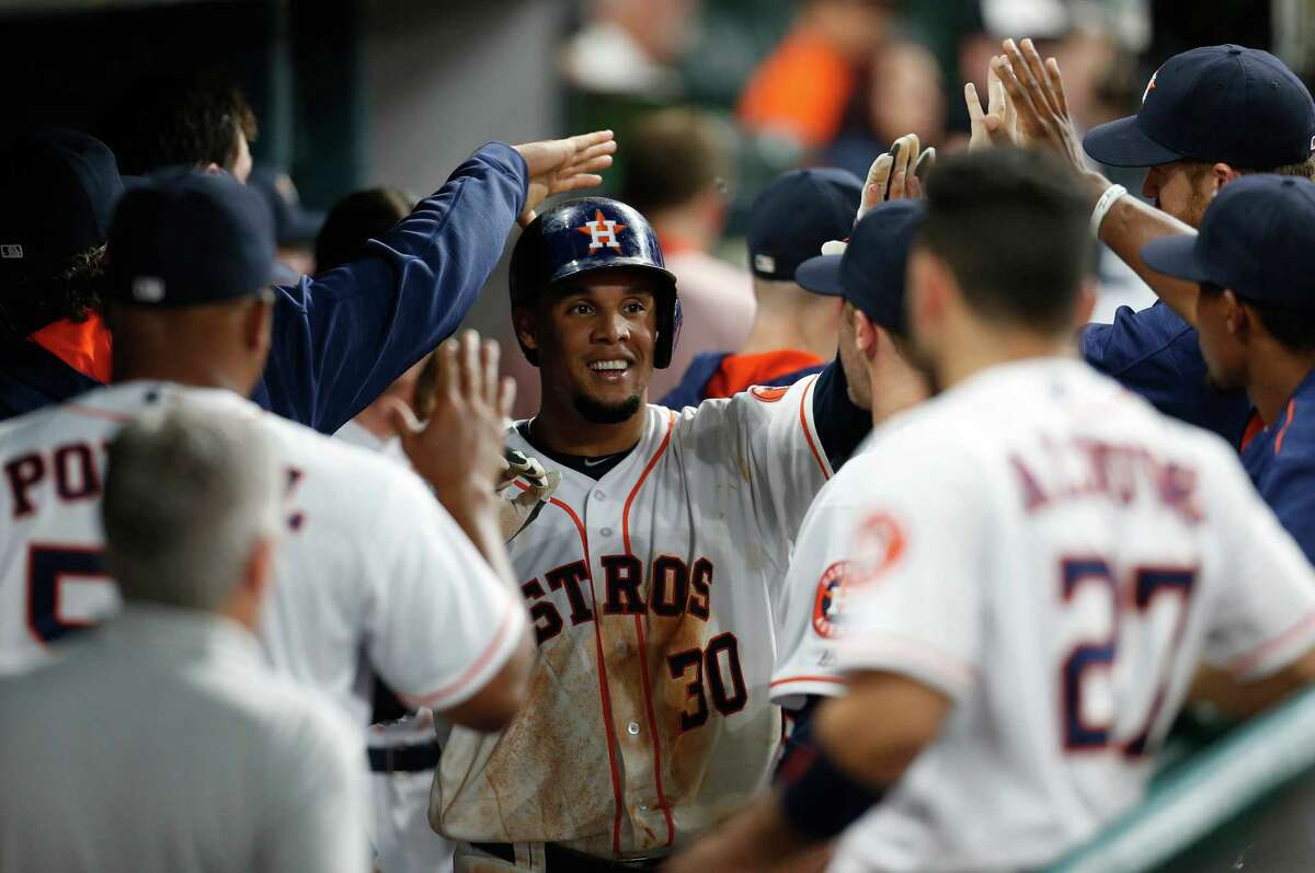 Houston Astros Carlos Gomez (30) celebrates his run scored on a single by Evan Gattis during the third inning of an MLB baseball game at Minute Maid Park, Monday, June 20, 2016, in Houston.
