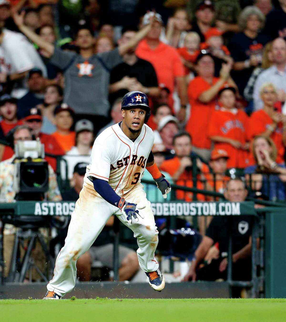 Houston Astros Carlos Gomez (30) tries to stop as he reached third base on a Luis Valbuena double during the third inning of an MLB baseball game at Minute Maid Park, Monday, June 20, 2016, in Houston.