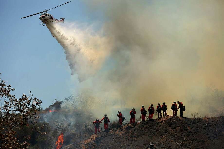 Firefighters in the air and on the ground work to control a fire that broke out in Duarte, Calif., near a neighborhood on Monday, June 20, 2016. Photo: Rick Loomis, TNS / Los Angeles Times