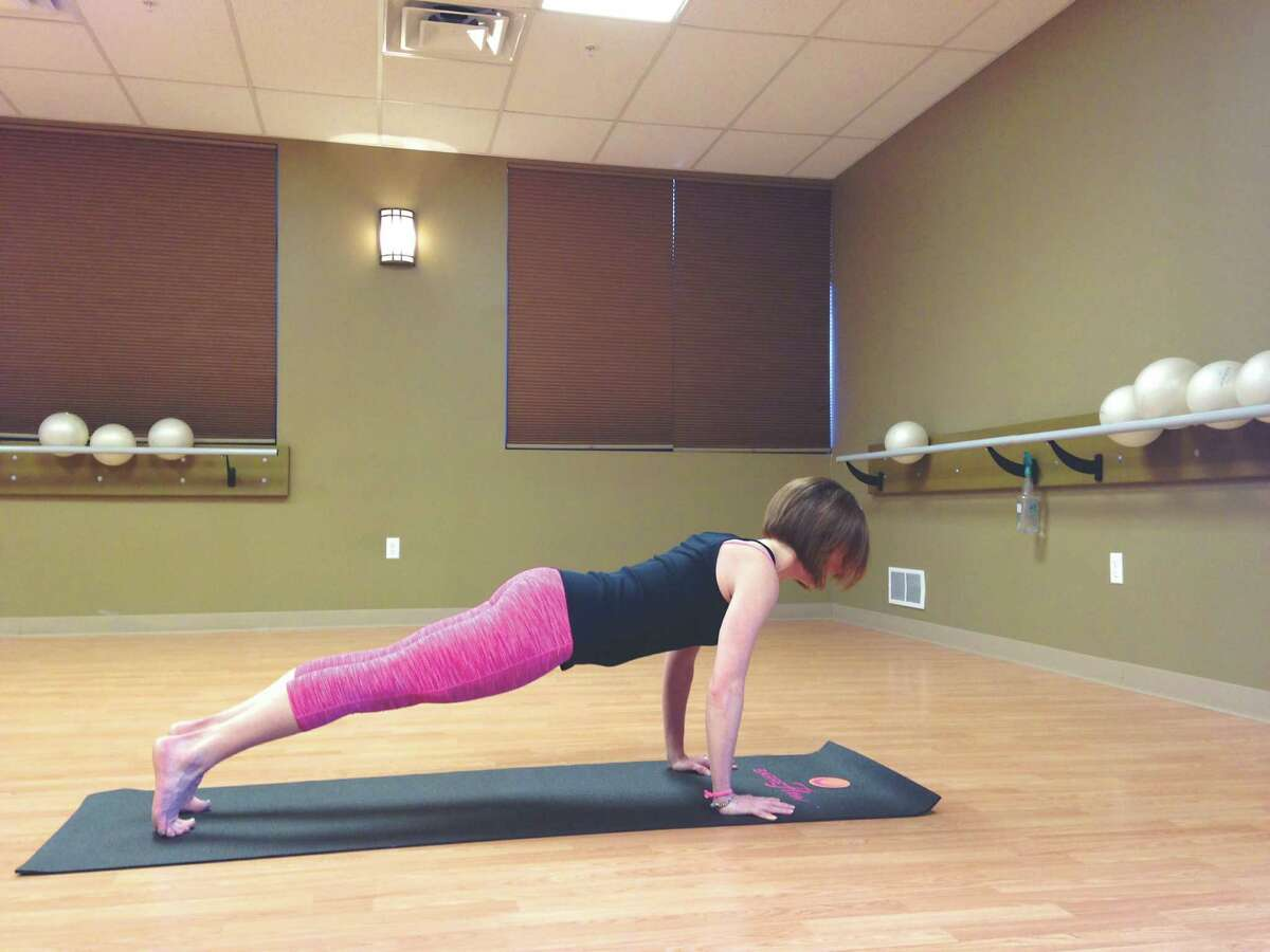 Karli Taylor creator of BarreFlow demonstrates proper Plank form. (Carin Lane / Times Union)