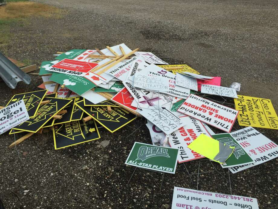 """Between 2008 and 2011, volunteers retrieved hundreds of """"bandit"""" signs similar to these that had been posted along rights of way on FM 1960."""