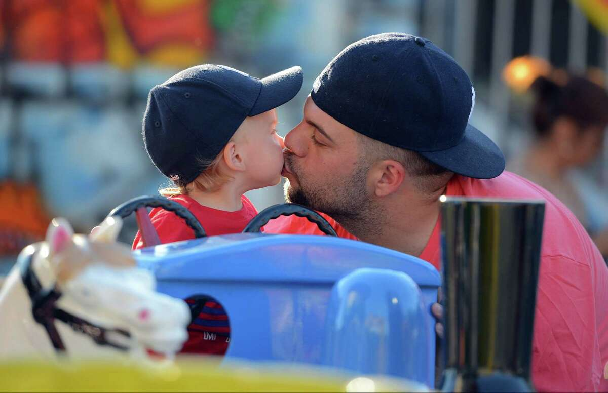 Michael Vitti of Darien, Conn. gets an early Father's Day kiss from his 19-month-old son Jay as the two enjoy the rides at the Family Fair at St. Mary Parish in Stamford, Conn. on Friday, June 17, 2016.