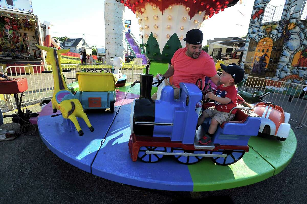Michael Vitti of Darien, Conn. and his 19-month-old son Jay enjoy the rides at the Family Fair at St. Mary Parish in Stamford, Conn. on Friday, June 17, 2016.