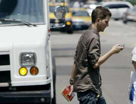 Giancarlo Yerkes, a 30-year-old advertising employee, crosses a street in downtown Chicago while text-messaging with his cell phone, Tuesday, July 29, 2008. In an alert issued this week, the American College of Emergency Physicians says based on reports from emergency-room doctors around the country, the number of text-messaging pedestrians, bicyclists, roller-bladers and even motorists who aren't so fortunate is rising. Terkes admitted he once walked straight into a stop sign while texting and bumped his head. (AP Photo/M. Spencer Green)