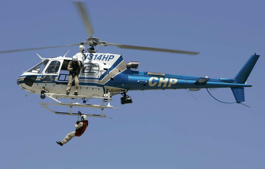 "A CHP helicopter based in Napa, pulls a man up from the ground in a demonstration at the ""Vertical Challenge Helicopter Show"" in San Carlos, CA, on Saturday, June 17, 2006. On Monday, a CHP helicopter crew rescued a couple stranded on Lake Sonoma. Photo: Darryl Bush, SFC"