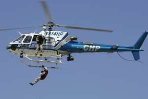 """avaitionshow_0002_db.JPG A CHP helicopter based in Napa, pulls a man up from the ground in a demonstration at the """"Vertical Challenge Helicopter Show,"""" held at Hiller Aviation Museum next to the San Carlos Airport in San Carlos, CA  on Saturday, June  17,  2006.  shot: 6/17/06 Darryl Bush / The Chronicle    **  (cq)"""