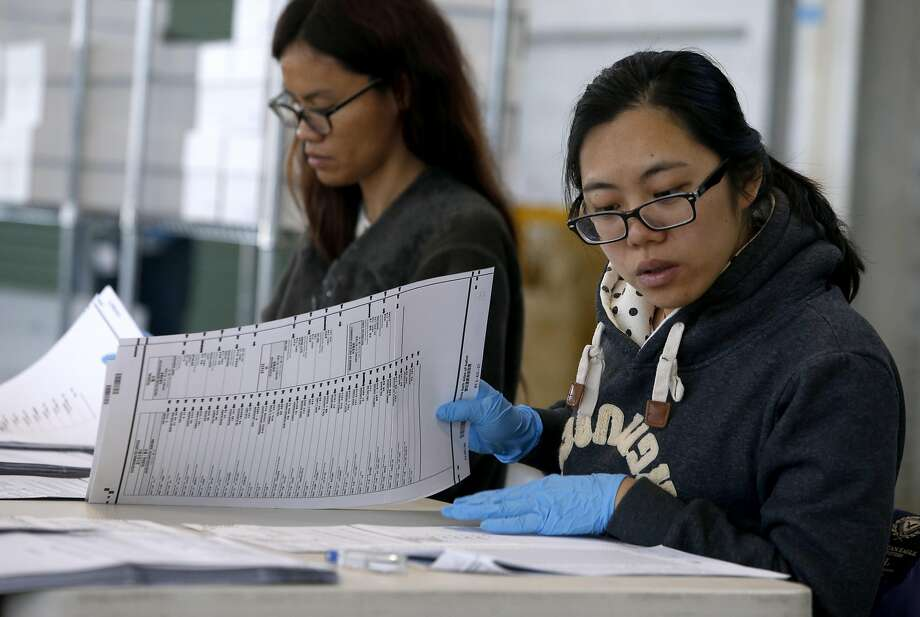 Iva Maurin (left) and Doris Lei hand-count ballots from the June 7 presi dential primary election two weeks later at Pier 48 in San Francisco. Photo: Paul Chinn, The Chronicle