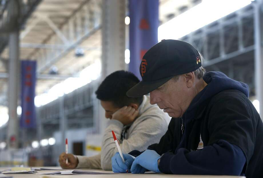 Kin Chu (left) and Robert Hutchings hand count ballots from the June 7 presidential primary election inside Pier 48 in San Francisco, Calif. on Tuesday, June 21, 2016. Teams of employees from the Department of Elections sift through every ballot from randomly selected precincts to ensure accuracy before the county's election results can be certified. Photo: Paul Chinn, The Chronicle