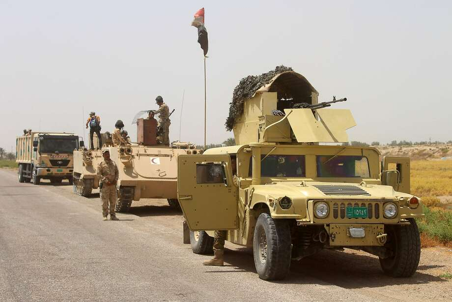 Government forces stand next to their vehicles as they hold a position southwest of the city of Fallujah. Photo: MOADH AL-DULAIMI, AFP/Getty Images