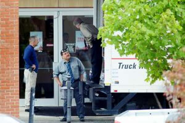 New York State Police load documents into a truck at Saratoga Nissan in Malta on May 9,2012. (Cindy Schultz/Times Union)