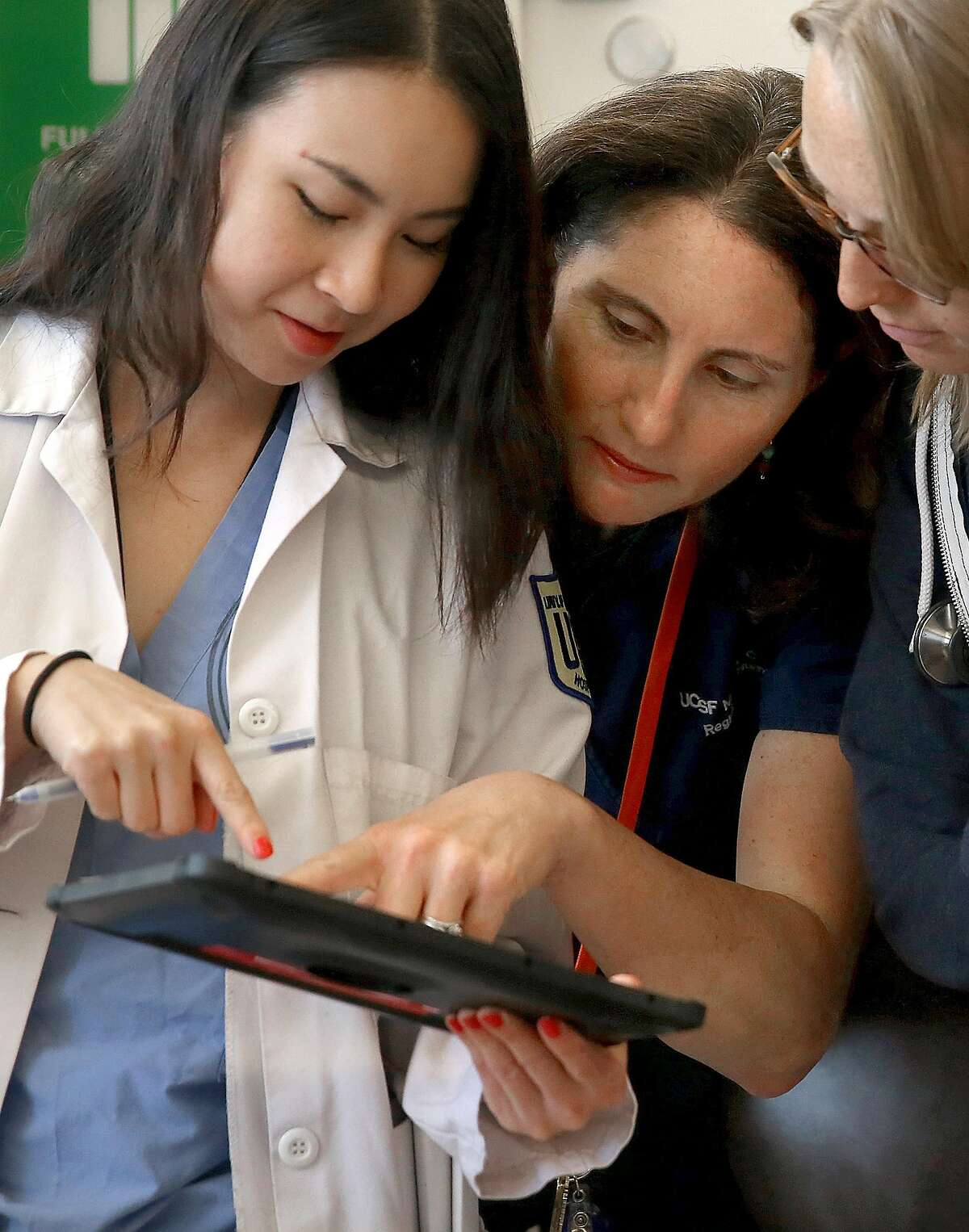 Denise Chang, MD (left) uses the software of Project Emerge on a tablet with Denise Barchas, RN (middle),and Laura Schoenher, MD (right) as the staff make patient rounds in an intensive care unit at UCSF hospital on Wednesday, June 15, 2016 in San Francisco, Calif.. UCSF and Johns Hopkins University School of Medicine are testing software they hope will improve intensive care.