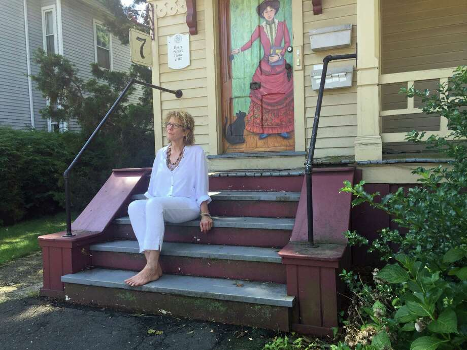 Bridgeport artist Elizabeth Hartstein sits in front of a door she recently painted for the house at 7 Berkley Street in Norwalk as part of an effort to introduce more public art in residential neighborhoods. Photo: Kaitlyn Krasselt / Hearst Connecticut Media / The Hour