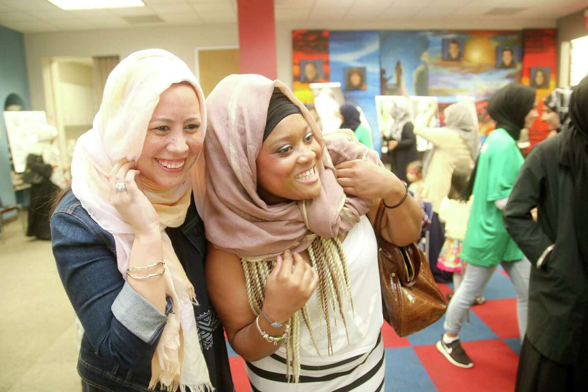 """Jisselle Campos, left, and Gabrielle Boykins look at themselves in the mirror after trying on a hijab, a headscarf worn by some Muslim women, at a """"Know Your Muslim Neighbor"""" event at Freeman Branch Library."""