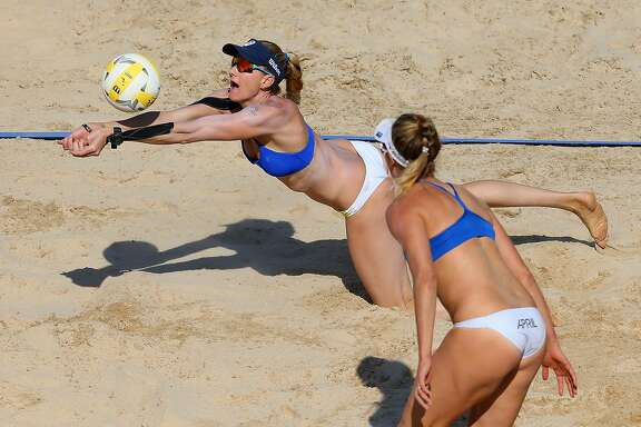 NEW YORK, NY - JUNE 19: Kerri Walsh Jennings dives for the ball as April Ross looks on against Lane Carico and Summer Ross during the Women's AVP New York Open Championship Match at Hudson River Park on June 19, 2016 in New York City. (Photo by Mike Stobe/Getty Images)
