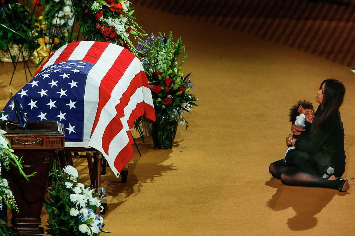 Lucy Lugo, wife of fallen Pearland police officer Endy Ekpanya, embraces and comforts their son, Julian Ekpanya, on the floor in front of his coffin during a funeral service at Grace Community Church Tuesday, June 21, 2016 in Houston.