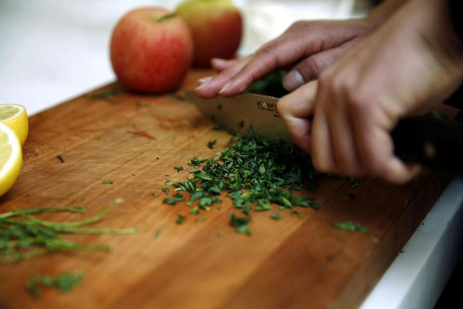 Amanda Haas, culinary director for Williams-Sonoma, chops tarragon in the test kitchen at Williams-Sonoma in S.F. Photo: Connor Radnovich, The Chronicle