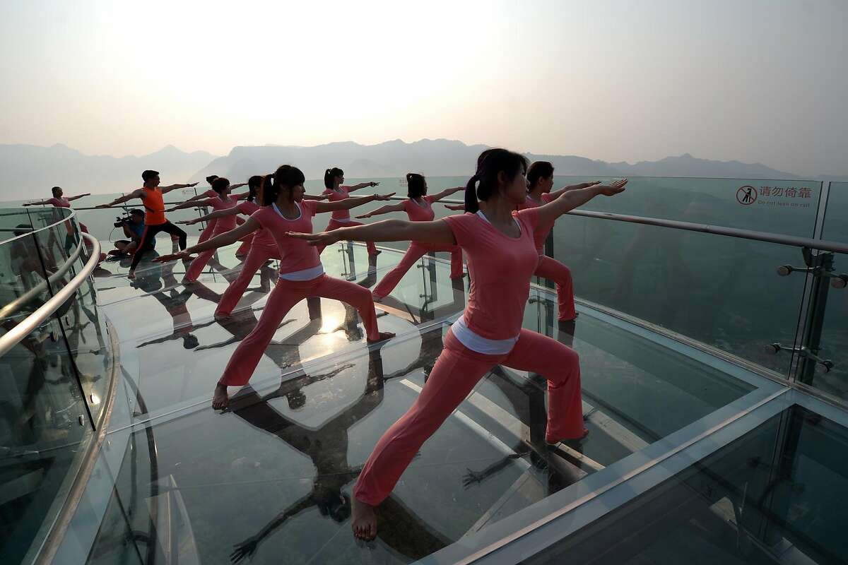 This photo taken on June 20, 2016 shows Chinese enthusiasts practicing yoga at a glass sightseeing platform in Shilinxia scenic area in Beijing. June 21 marks the International Yoga Day. / AFP PHOTO / STR / China OUTSTR/AFP/Getty Images