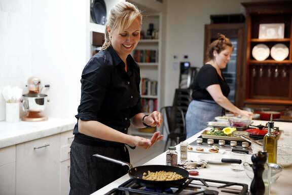 Amanda Haas (left), culinary director for Williams-Sonoma, cooks as test cook Belle English arranges a food tasting in the test kitchen at Williams-Sonoma in San Francisco, California, on Monday, June 20, 2016.