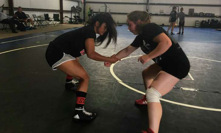 Madison Angelito (left) and Aspen Teeples practice freestyle wrestling at the NB Elite Wrestling gym. The club is one of the state's premier wrestling groups.