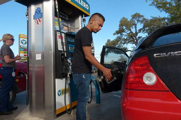 Charles Flores pumps gas at the Valero Station at 5602 UTSA Blvd on Friday, Oct. 31, 2014.