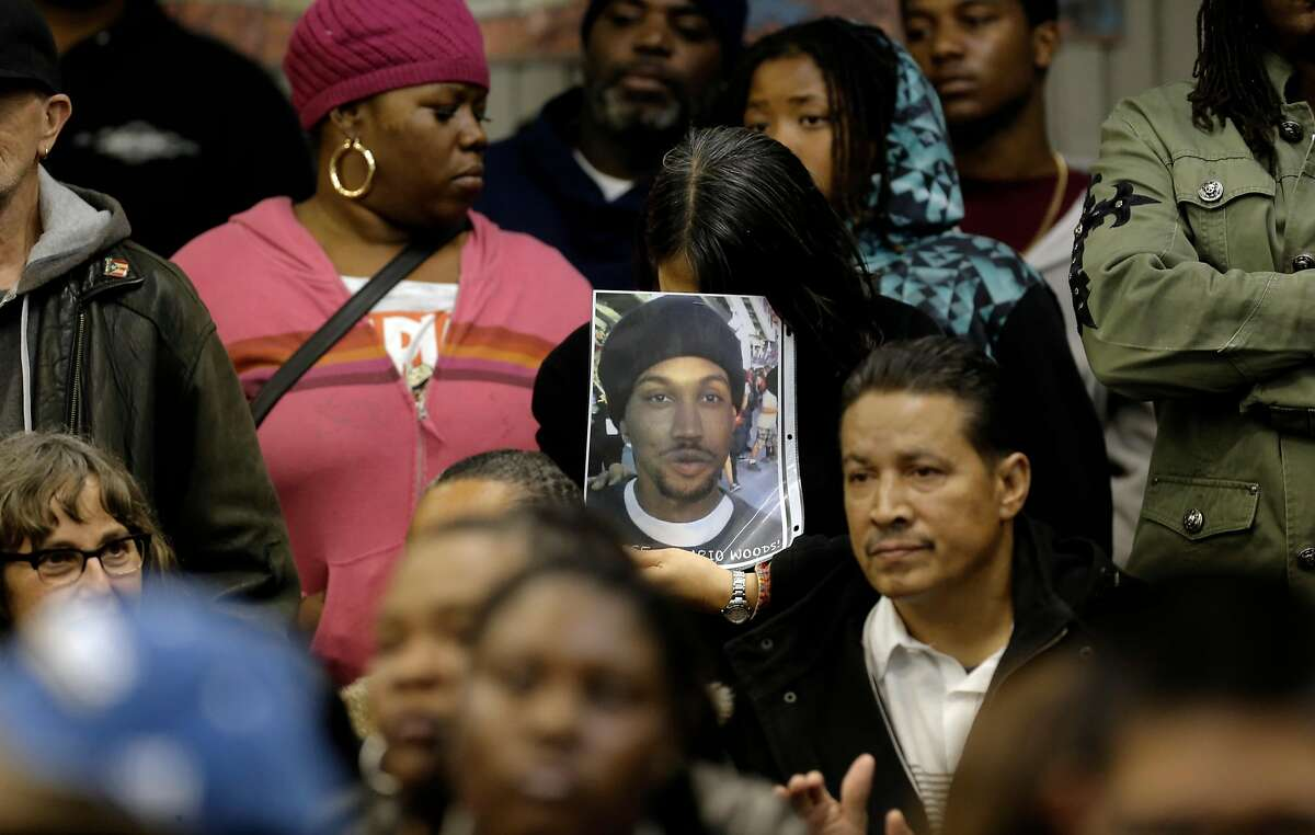 A woman holds a photo of Mario Woods as the San Francisco Police department hosts a town hall meeting Dec. 4, 2015.