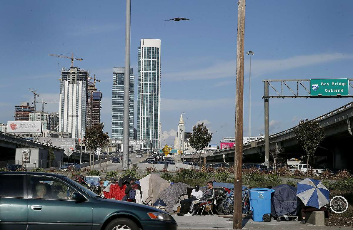 With new construction looming in the background, residents of the encampment near the 5th Street Bay Bridge onramp sat outside their tents Tuesday March 3, 2015.