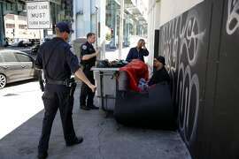 San Francisco Police officers Suhrke (left) and Gerrans tell Mele (center) and Junior, a homeless couple, to move their encampment from the sidewalk near Division and Bryant streets in San Francisco, California, on Wednesday, Aug. 12, 2015.