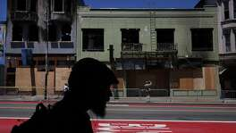 Businesses are seen boarded up after a five-alarm fire raged through them over the weekend on Mission street June 21, 2016 in San Francisco, Calif.