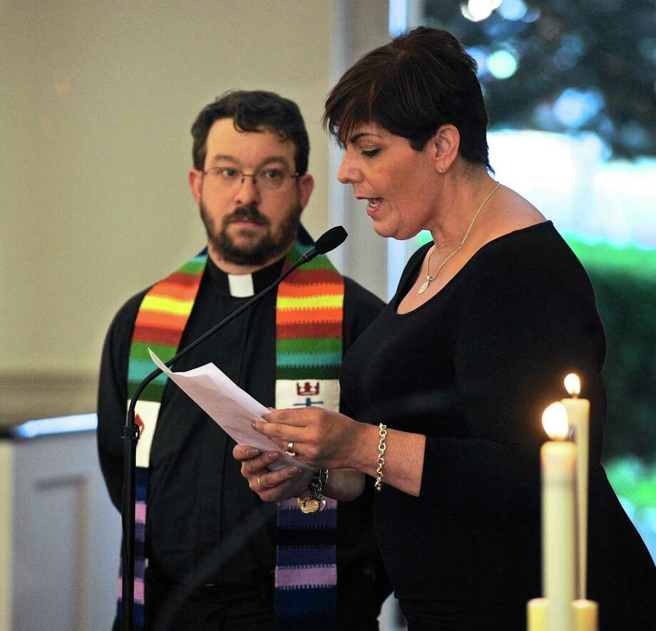 The Rev. Paul Bryant-Smith, from the King Street United Church of Christ, in Danbury, looks on as Migdalia Ballester Alicea, a community Liaison from Congresswoman Elizabeth Esty's office, reads from a list of names of those killed in the nightclub shooting in Orlando, Fl, during a vigil at the First Congregational Church of Danbury on Tuesday evening, June 21, 2016, in Danbury, Conn. Photo: H John Voorhees III / Hearst Connecticut Media / The News-Times