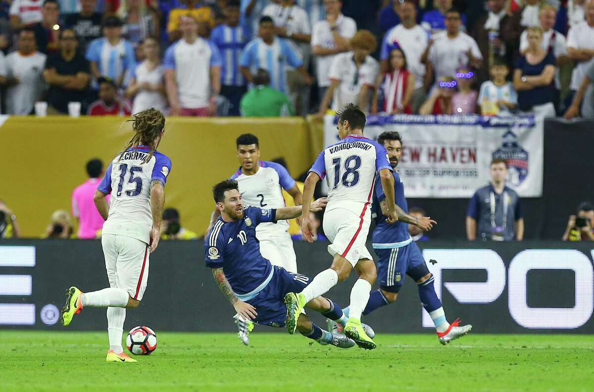 Argentina midfielder Lionel Messi (10) falls after contact with United States forward Chris Wondolowski (18), setting up a penalty kick where Messi scored a goal during the first half of a COPA America semi-final game at NRG Stadium, Tuesday, June 21, 2016, in Houston.