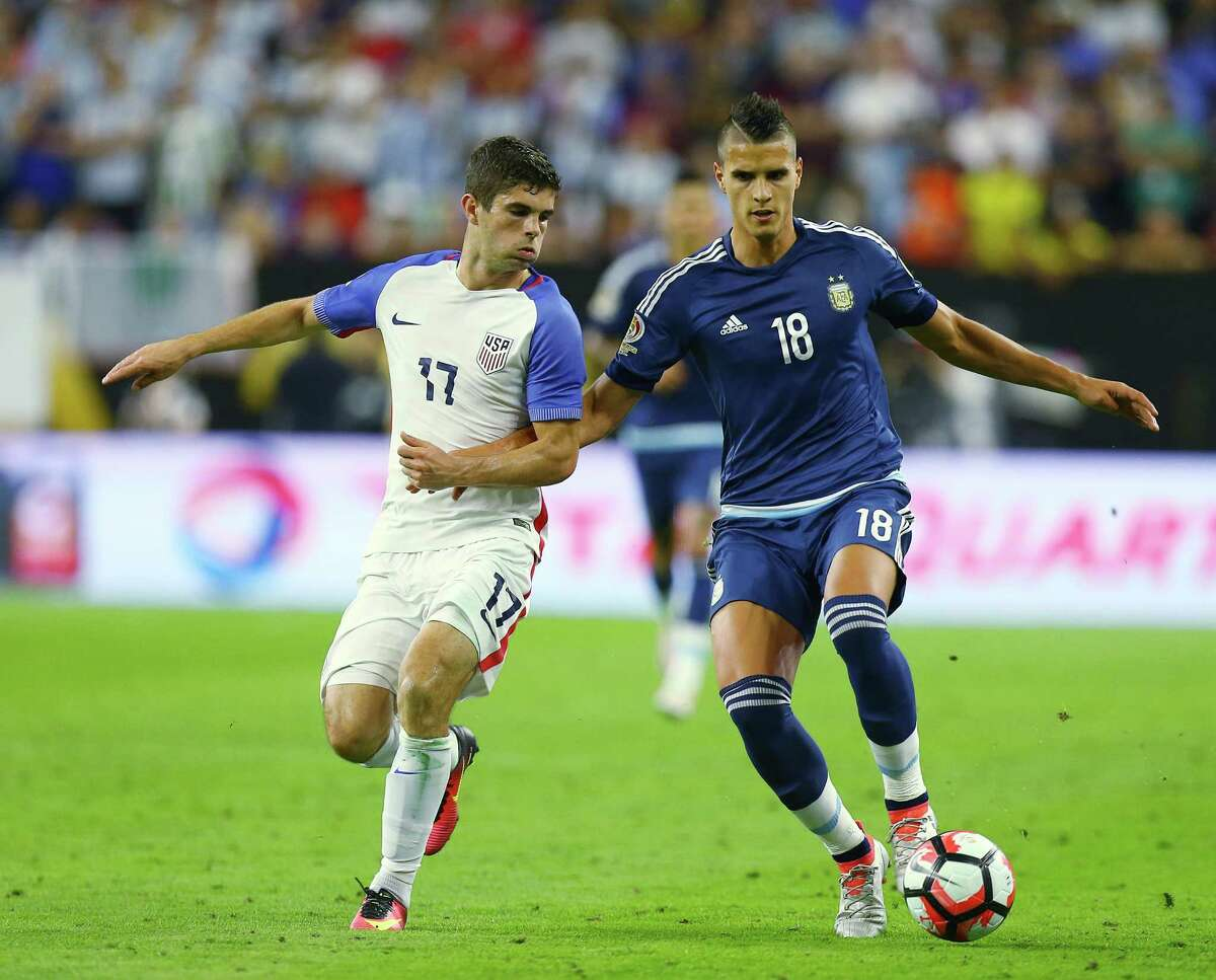Argentina forward Erik Lamela battles United States midfielder Christian Pulisic (17) for possession during the second half of a COPA America semi-final game at NRG Stadium, Tuesday, June 21, 2016, in Houston.