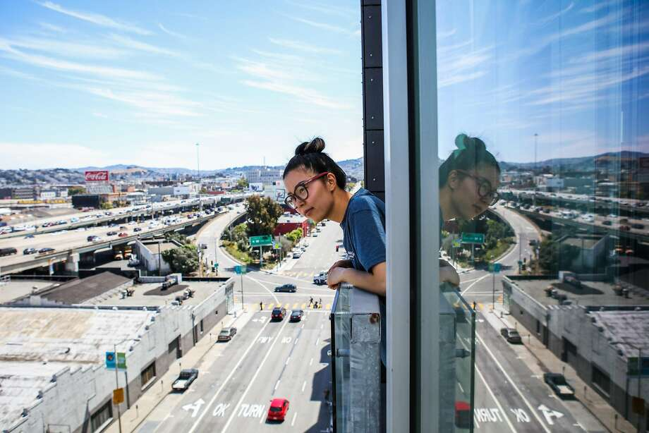 Cece Lok looks out at the view from the porch of a tiny apartment, during an open house at the Cubix building, in San Francisco, California, on Sunday, June 19, 2016. Photo: Gabrielle Lurie, Special To The Chronicle