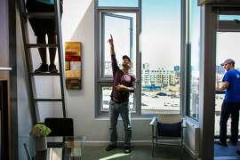 (l-r) Ro-El Cordero, Jason Schmidt, and Andrew Buck explore a tiny apartment, during an open house at the Cubix building, in San Francisco, California, on Sunday, June 19, 2016.